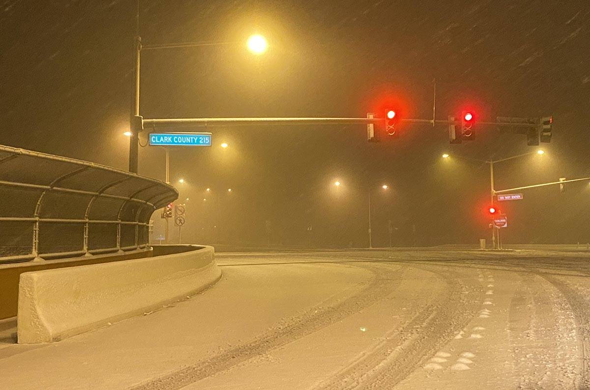 Snow covers much of the intersection at West Lake Mead Boulevard and the 215Beltway before sunr ...