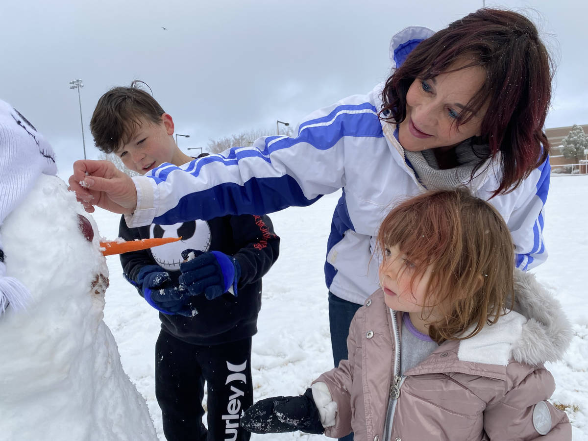 Lisa Hauger, center, makes a snowman with her grandchildren, Rylie OՂrien, 3, and Brody O ...