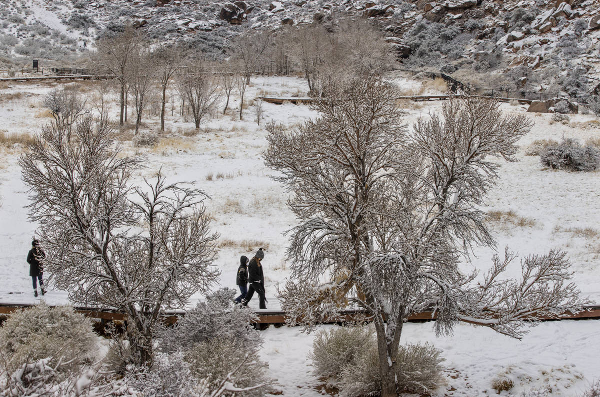 People walk in the snowfall about Calico Basin in the Red Rock Conservation Area on Tuesday, Ja ...