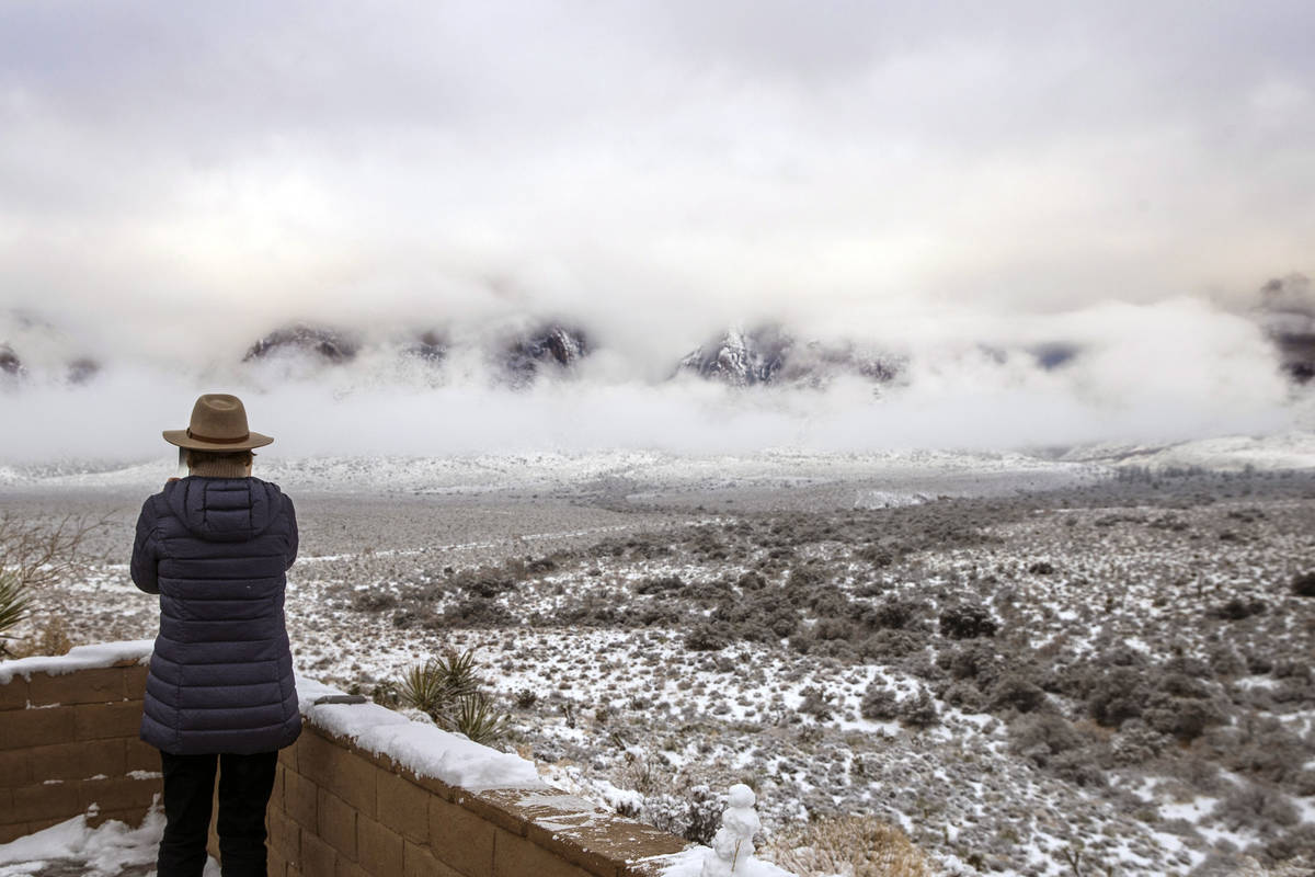 The clouds begin to break about the mountain range near the overlook in the Red Rock Conservati ...