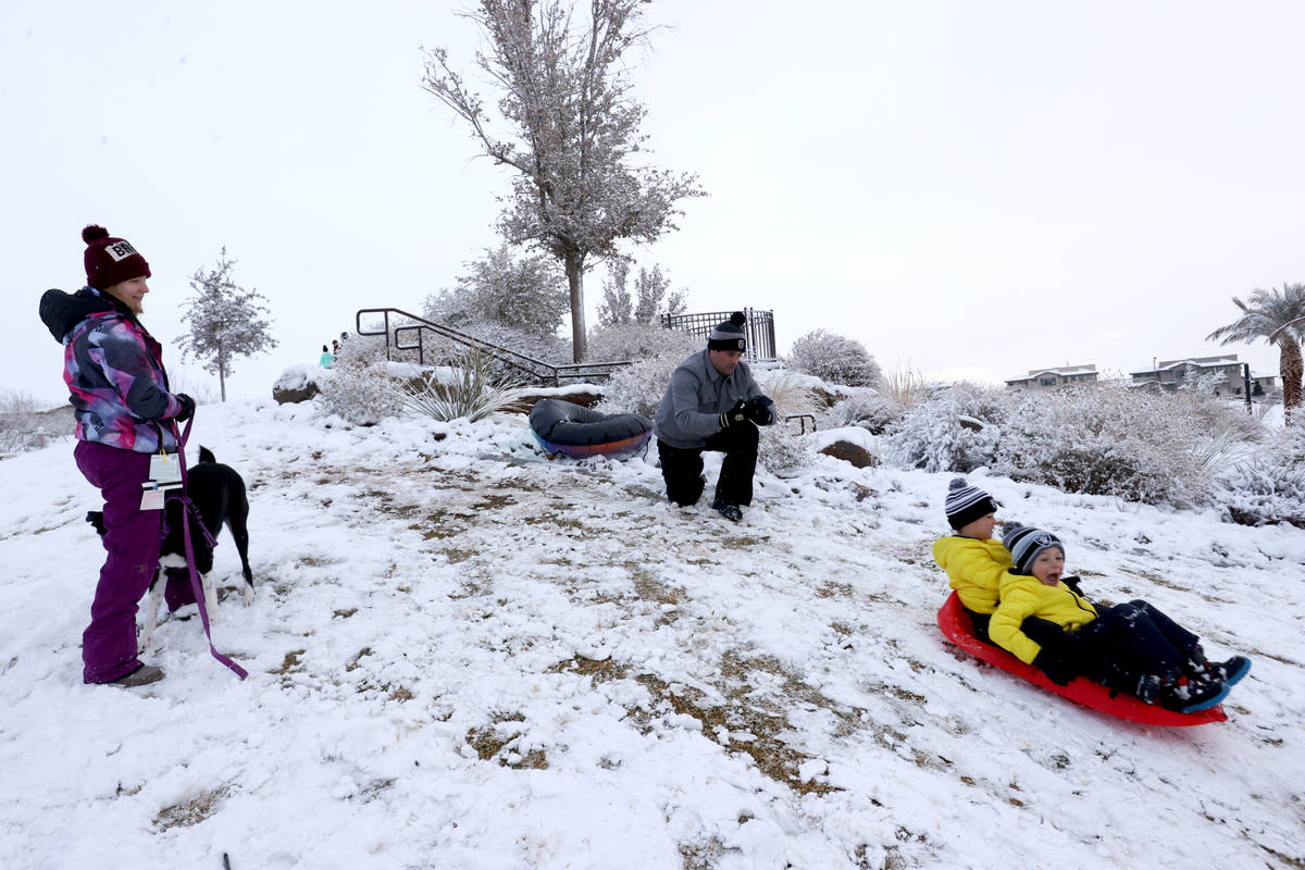 Nicholas Tarantino, 7, left, and his brother, Colton, 5, slide down a hill as their mother Eric ...