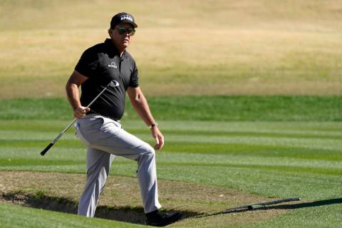 Phil Mickelson walks out from a bunker after hitting to the 17th green during the first round o ...