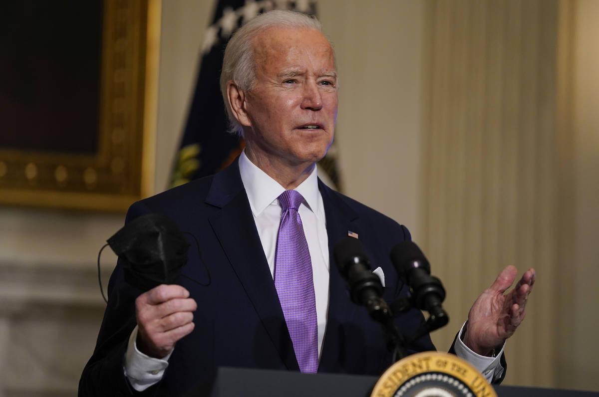 In a Jan. 26, 2021, photo, President Joe Biden holds his face mask as he speaks on COVID-19, in ...