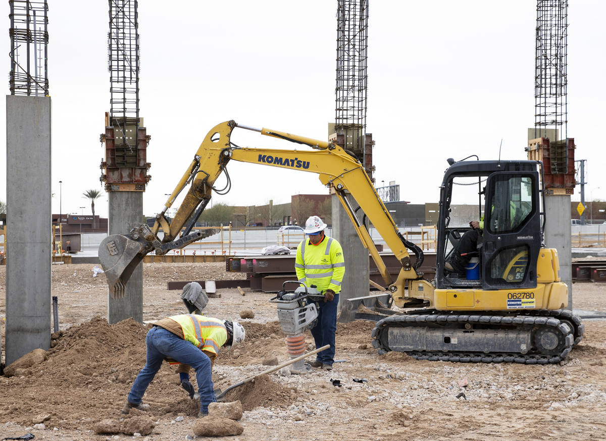 A Construction worker uses compactor to firm soil at the construction site of Axiom, an office ...