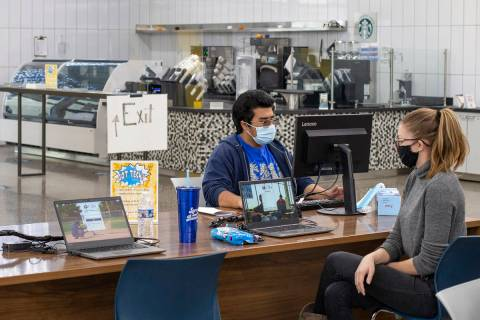 Daniel Herrera, a freshman at the College of Southern Nevada, checks out his new laptop at CSN' ...