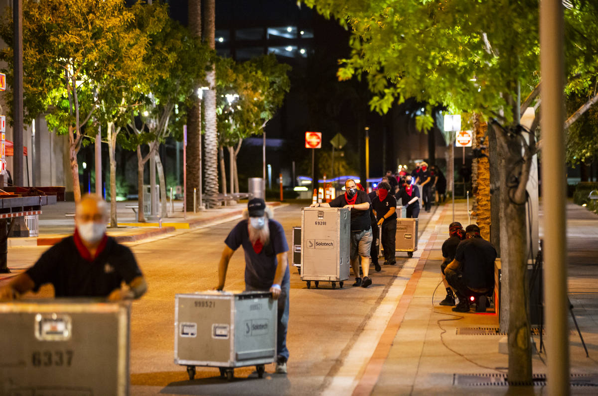"Entertainment workers push road cases around The Smith Center as it turns red for the ""Red ..."
