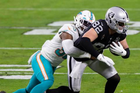 Miami Dolphins outside linebacker Jerome Baker (55) tackles Raiders tight end Jason Witten (82) ...