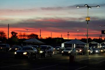 Vehicles wait for COVID-19 vaccination cards during a pre-registered drive-thru event at State ...