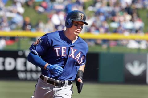 Texas Rangers' Drew Robinson heads to third during the second inning of a spring training baseb ...