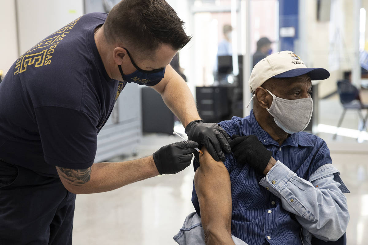 North Las Vegas Fire Department Batallion Chief Jeff Hurley administers the COVID-19 vaccine to ...