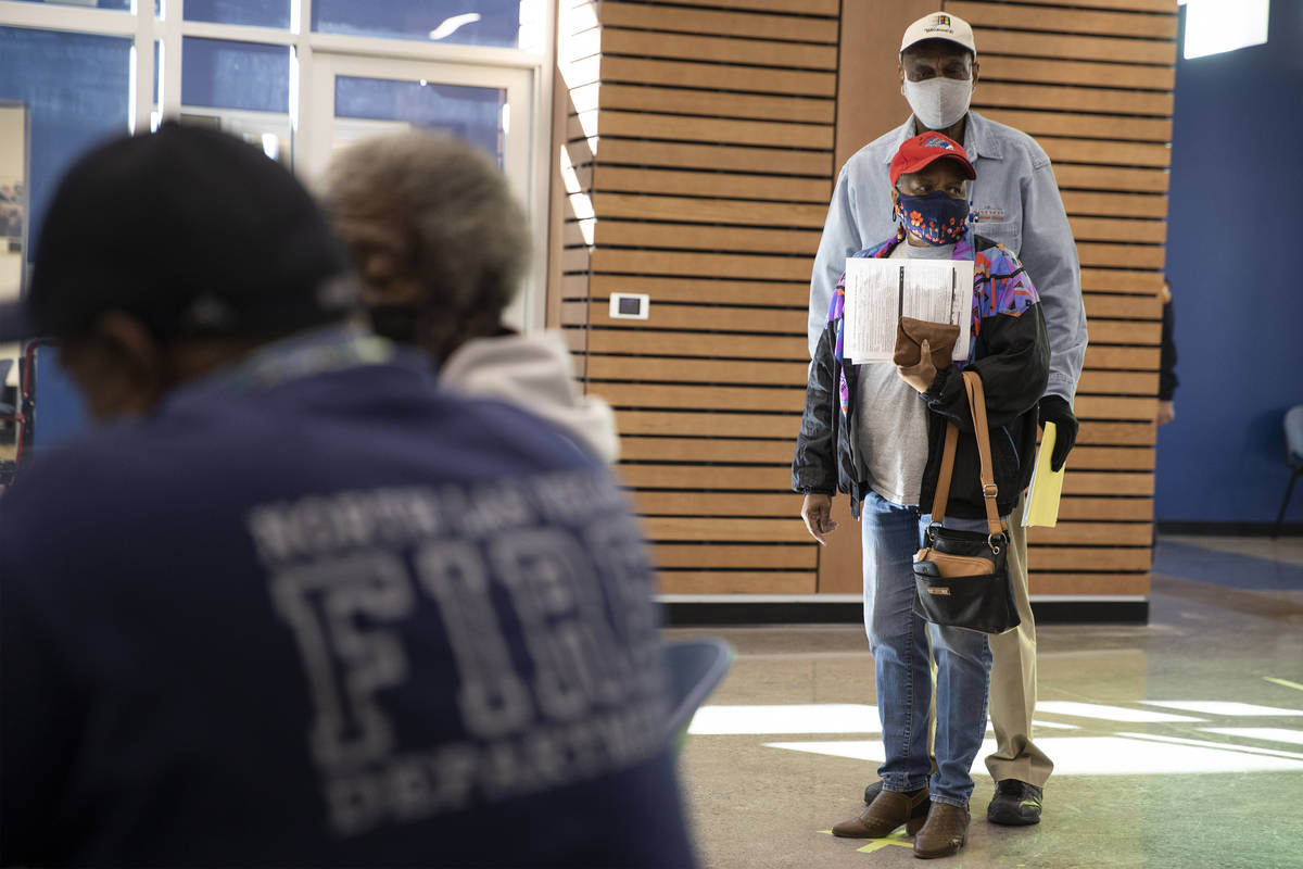 Ernest Conner, rear, and his wife Henrietta Peterson, wait in line to get the COVID-19 vaccine ...