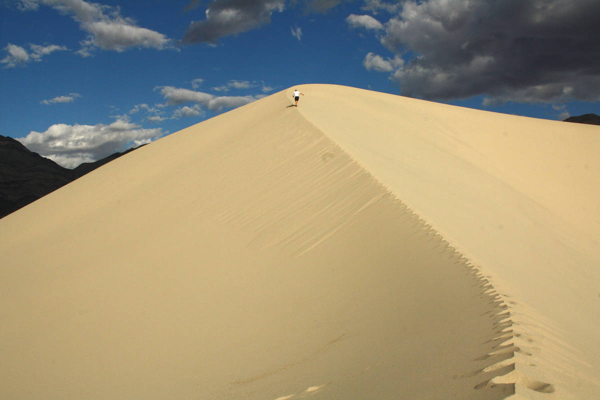 A hiker makes his way up the soft sand at Eureka Dunes. (Deborah Wall)