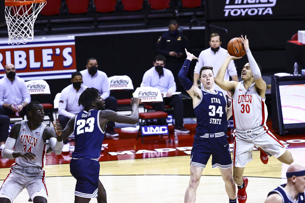 UNLV Rebels forward Devin Tillis (30) shoots over Utah State Aggies forward Justin Bean (34) du ...
