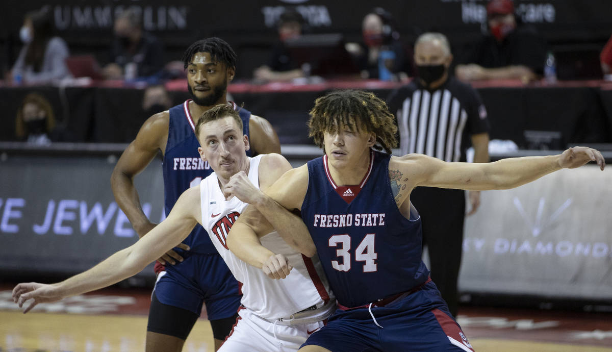 UNLV Rebels forward Moses Wood (1) fights for a loose ball with Fresno State Bulldogs center Br ...