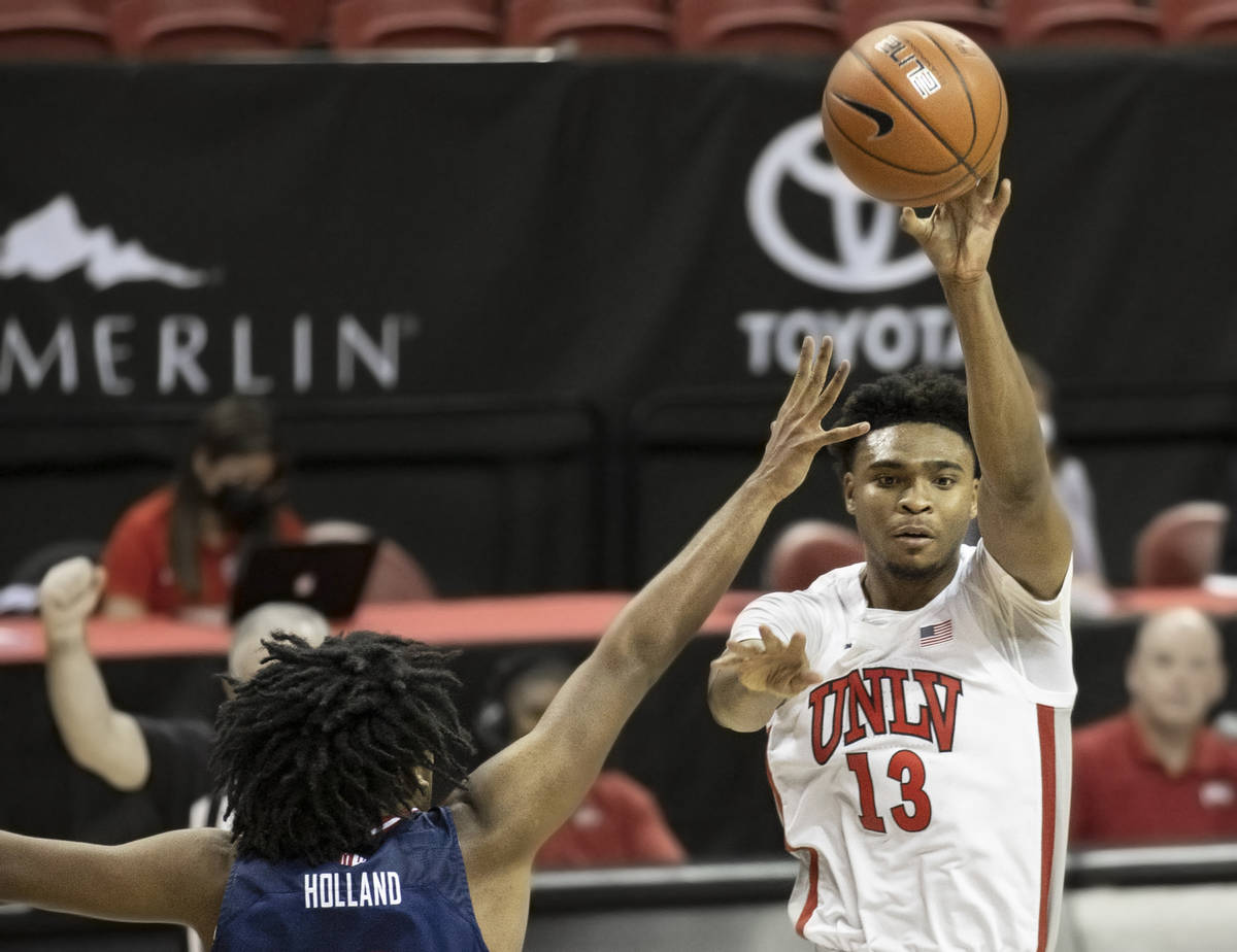 UNLV Rebels guard Bryce Hamilton (13) passes the ball over Fresno State Bulldogs guard Anthony ...
