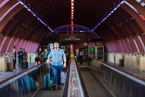 Visitors exit McCarran International Airport on Sunday, Nov. 22, 2020, in Las Vegas. (Ellen Sch ...