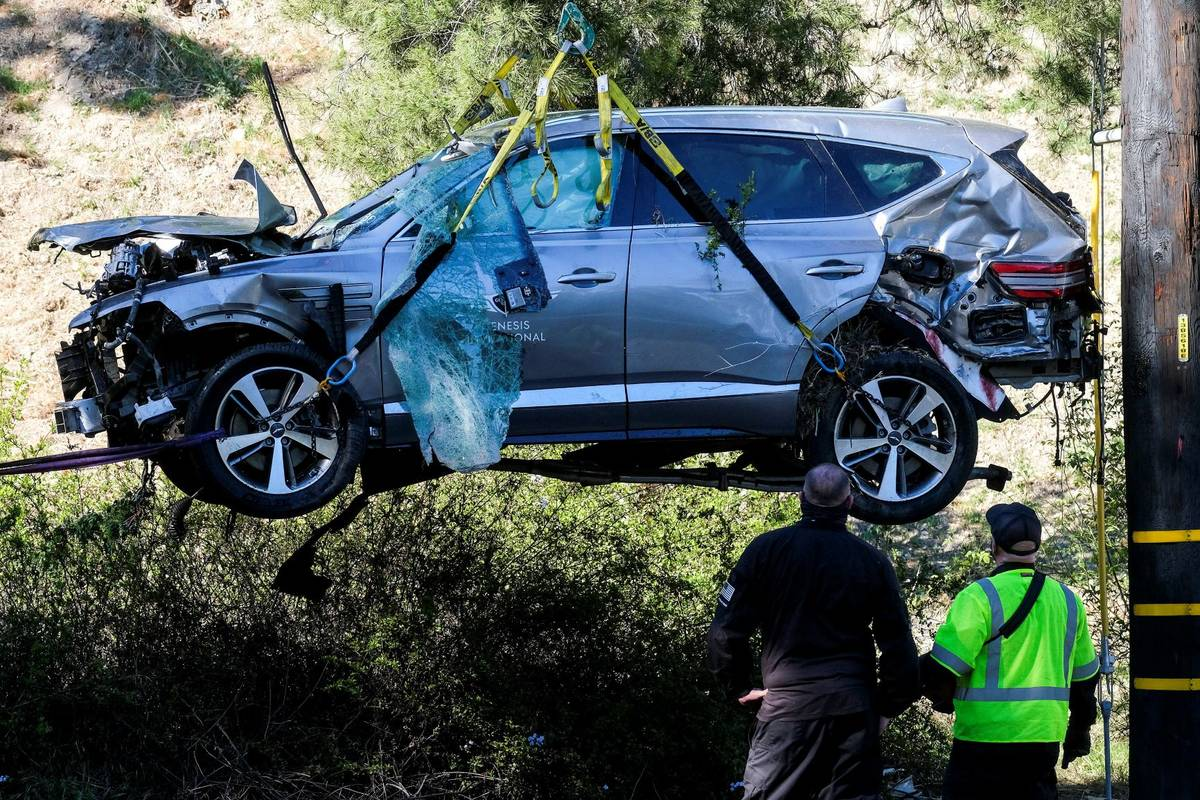 Workers watch as a crane is used to lift a vehicle following a rollover accident involving golf ...