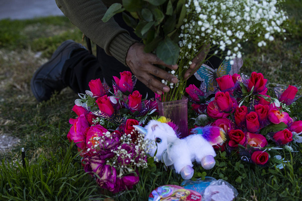 Brian Bradford arranges roses and flowers by the grave of his daughter, Briana Bradford, on the ...