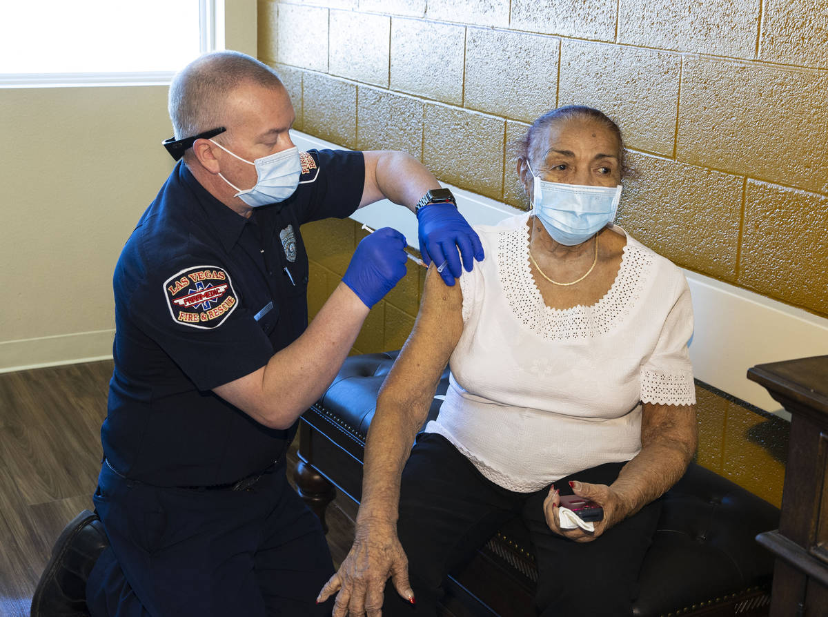 Chris Racine of Las Vegas Fire Rescue administers a COVID-19 vaccine to Rosa Nunez, 92, a resid ...