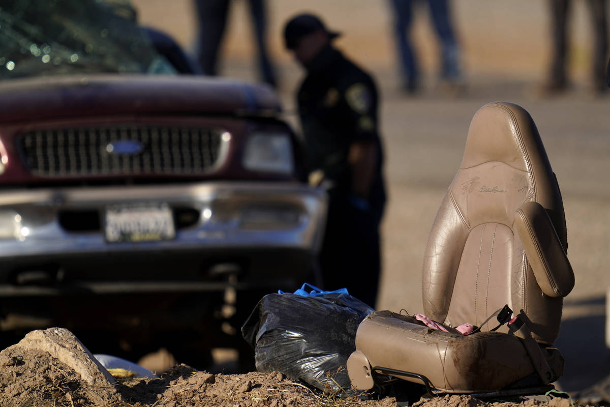 A law enforcement officer examines the scene of a deadly crash in Holtville, Calif., Tuesday, M ...