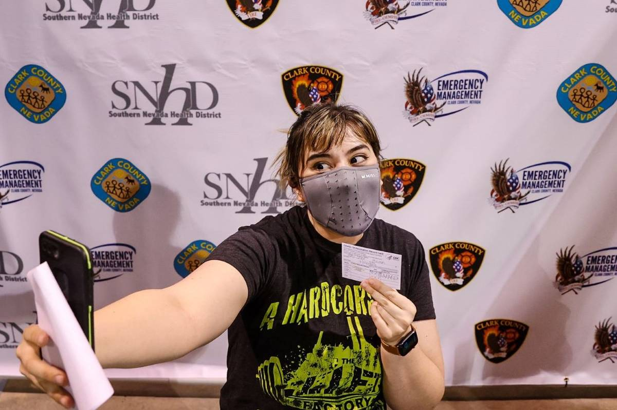 """Micah Haji-Sheikh, 27, of North Las Vegas takes a photo in the """"Selfie Station"""" after receiving ..."""