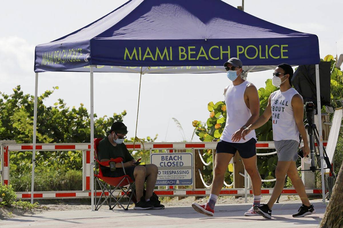 People wearing protective face masks walk past a closed entrance to the beach during the new co ...