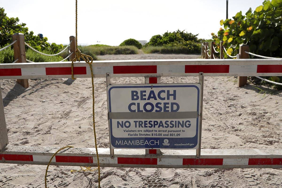 A sign is posted at a closed entrance to the beach during the new coronavirus pandemic, Friday, ...
