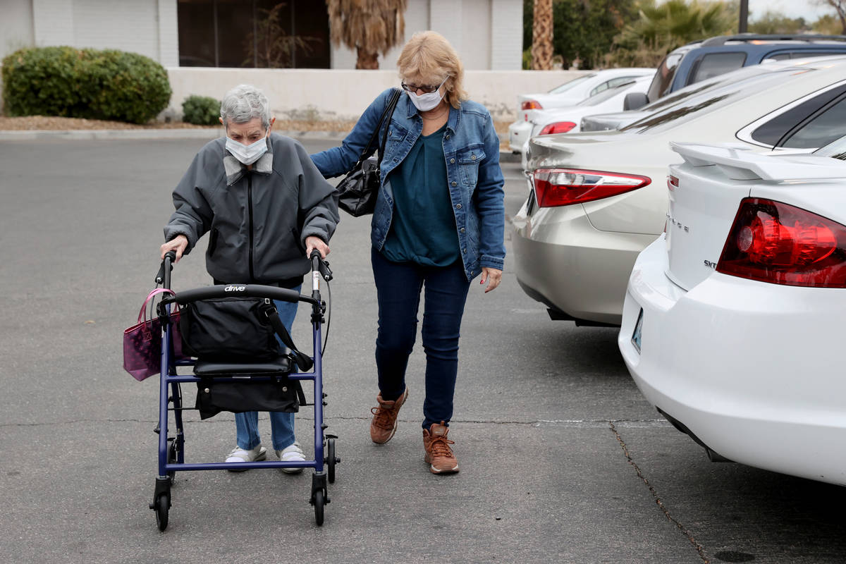 Estelle Roberts, 92, gets help from her daughter Dori Roberts-Lombardi, 65, before a doctor's a ...