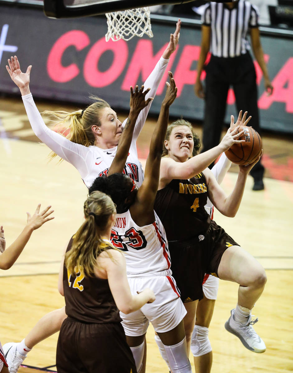 Wyoming Grace Ellis (4) pushes past UNLV center Desi-Rae Young (23) for a basket in the second ...