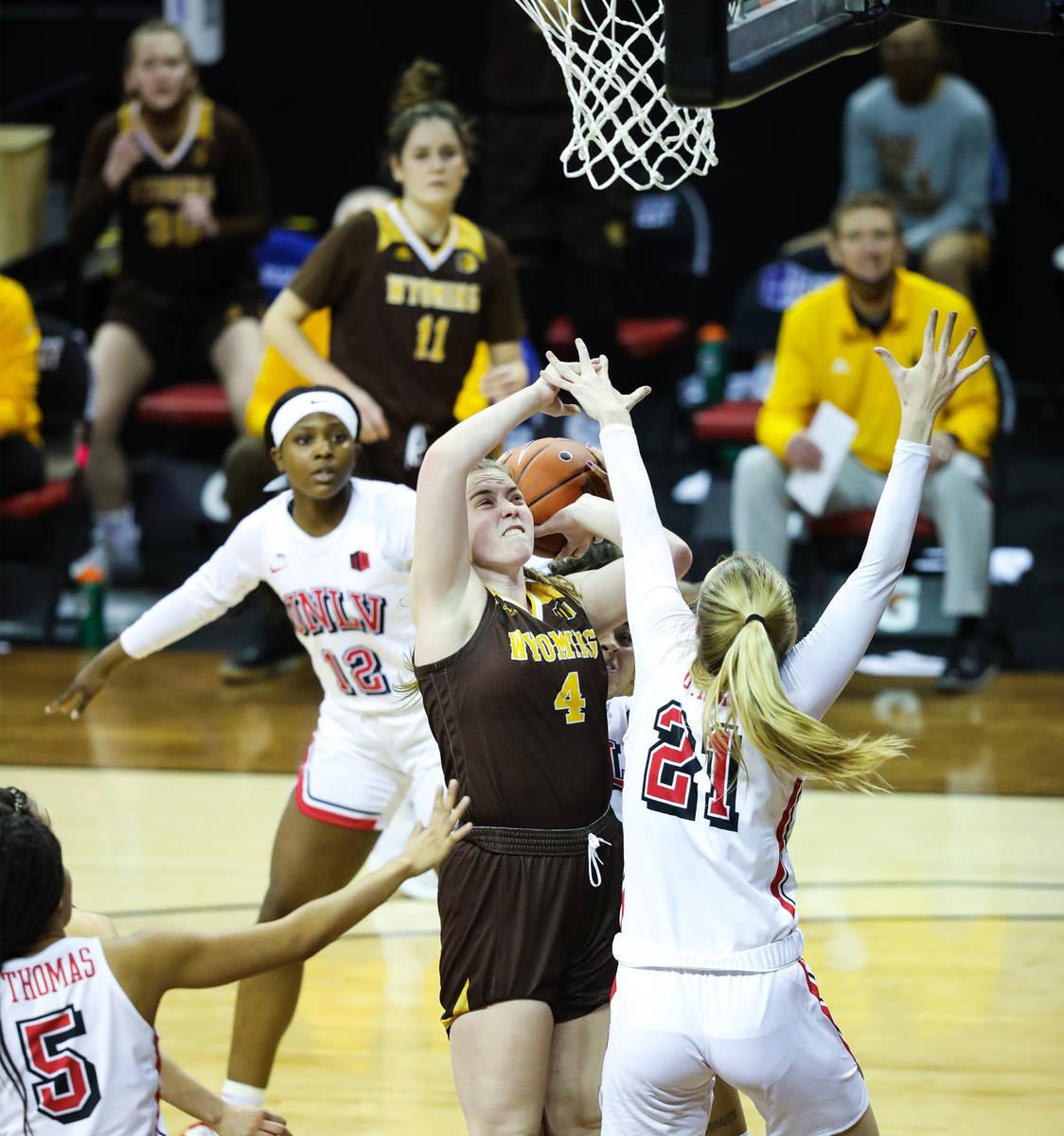 Wyoming guard Grace Ellis (4) shoots a basket against UNLV center Delaynie Byrne (21) in the se ...