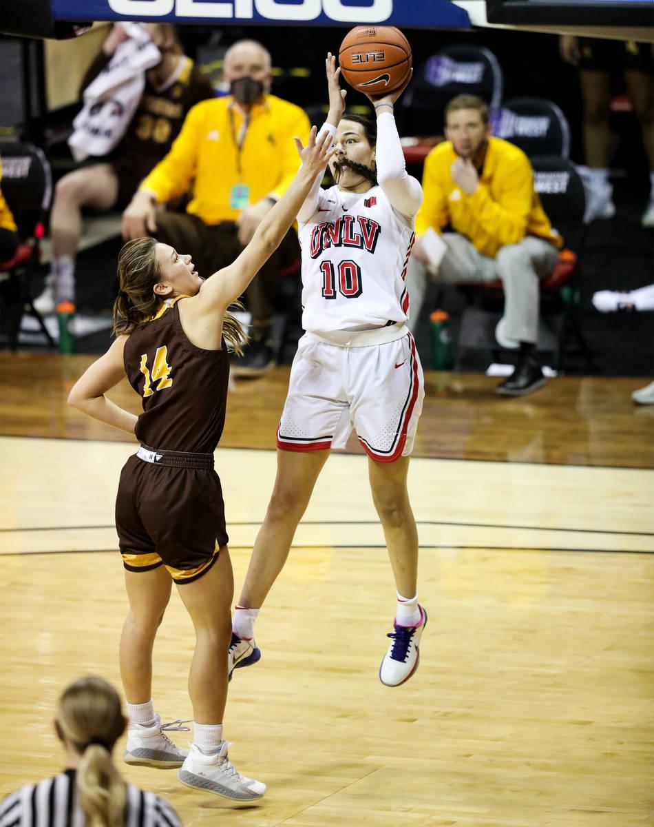 UNLV guard Jacinta Buckley (10) attempts a basket against Wyoming guard Quinn Weidemann (14) in ...