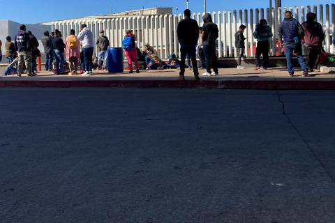 Migrants waiting to cross into the United States wait for news at the border crossing Wednesday ...