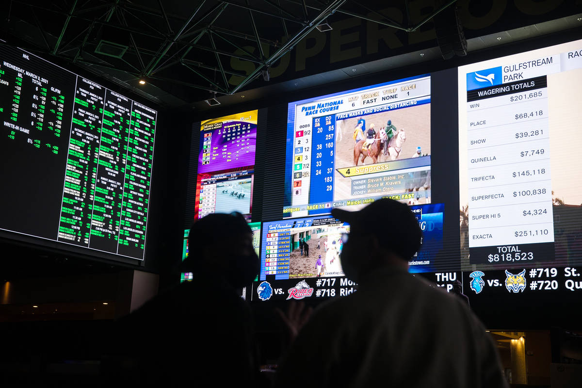 Bob Butler, left, and Richard Hoffman, right, watch the betting screens at the Westgate sportsb ...