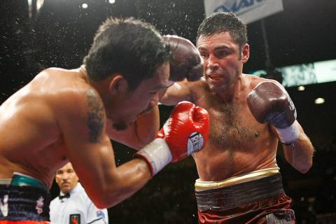 Boxer Manny Pacquiao, left, takes a blow from his opponent Oscar De La Hoya during their welter ...