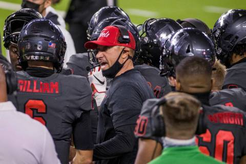 UNLV Rebels head coach Marcus Arroyo, center, speaks to quarterback Max Gilliam (6) and other ...