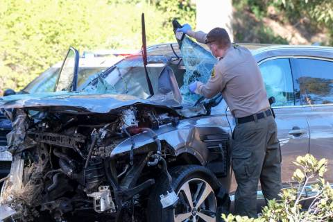 A law enforcement officer looks over a damaged vehicle following a rollover accident involving ...