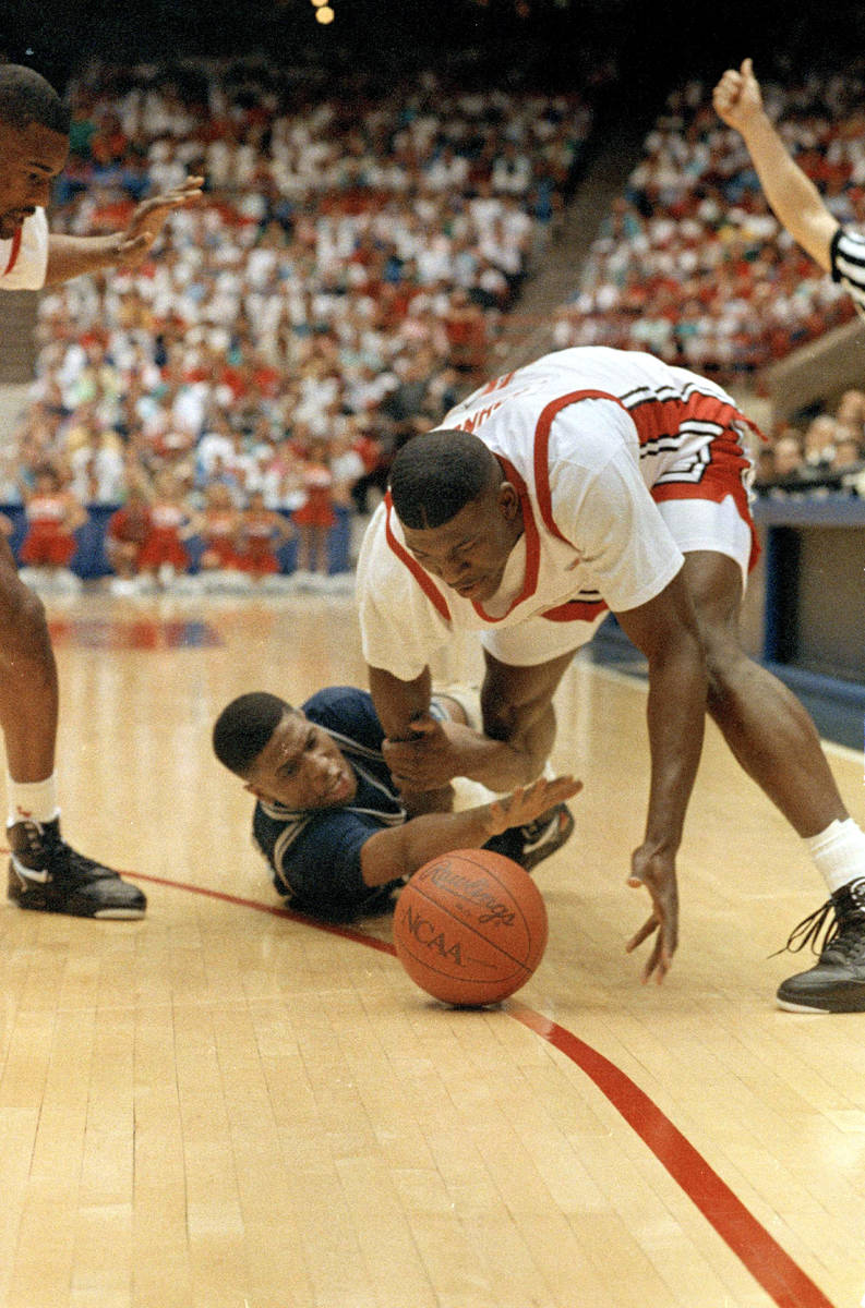 UNLV's Larry Johnson manages to get the ball away from Georgetown's Robert Churchwell during ac ...
