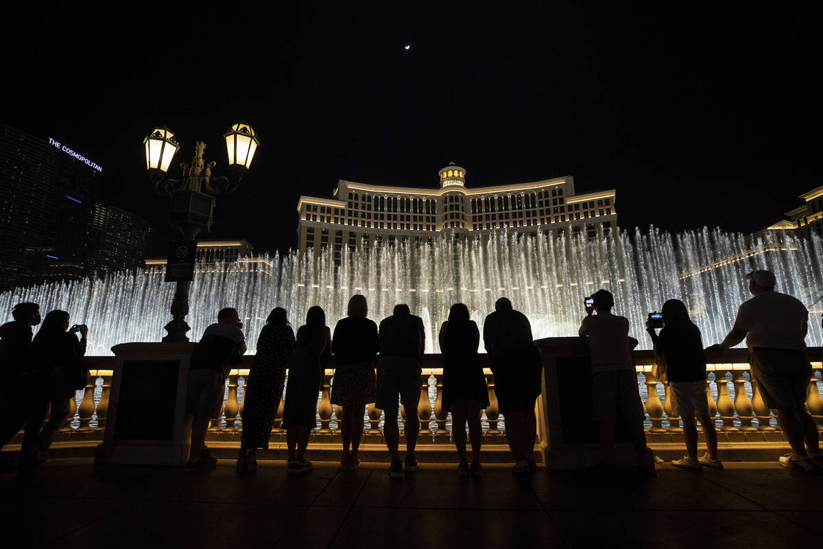 Visitors enjoy the Fountains of Bellagio show on Friday, March 19, 2021, in Las Vegas. (Benjami ...