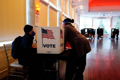 In this Nov. 3, 2020, file photo, a poll worker talks to a voter before they vote on a paper ba ...