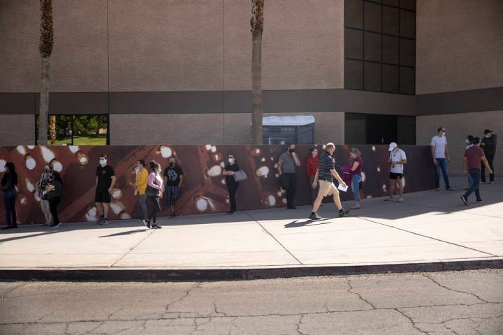 People wait in line to receive the COVID-19 vaccine at the Cashman Center in Las Vegas, April 6 ...