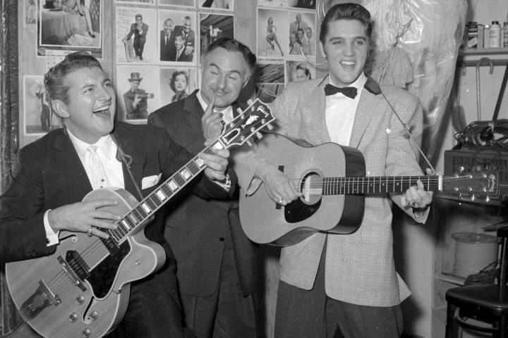 Liberace jokes around on a guitar as he and his brother George Liberace visit Elis Presley back ...