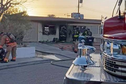 North Las Vegas firefighters investigate a house fire on Webster Circle in North Las Vegas on T ...