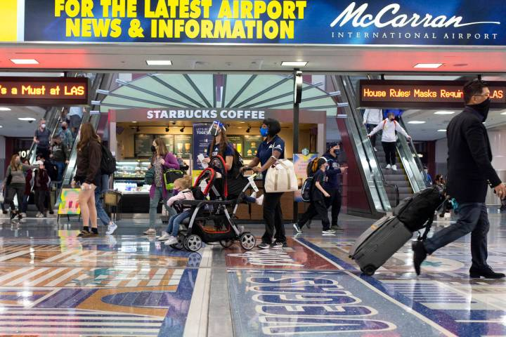 People move throughout baggage claim, wearing personal protective equipment to prevent the spre ...