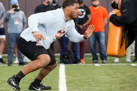 Christian Darrisaw runs a drill Virginia Tech pro day, attended by NFL football scouts, in Blac ...
