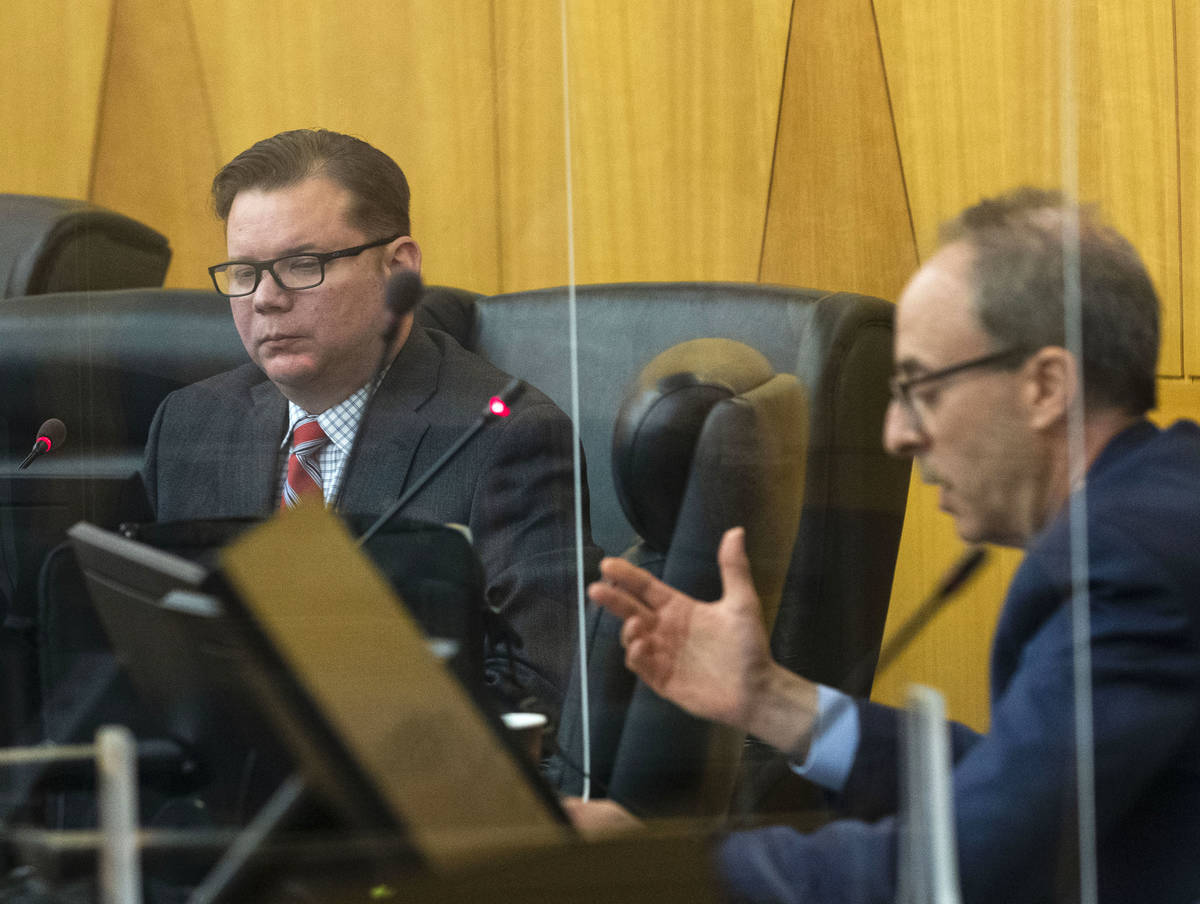 Hearing officer Chip Sigel, right, reads a question from the public to Las Vegas police detecti ...