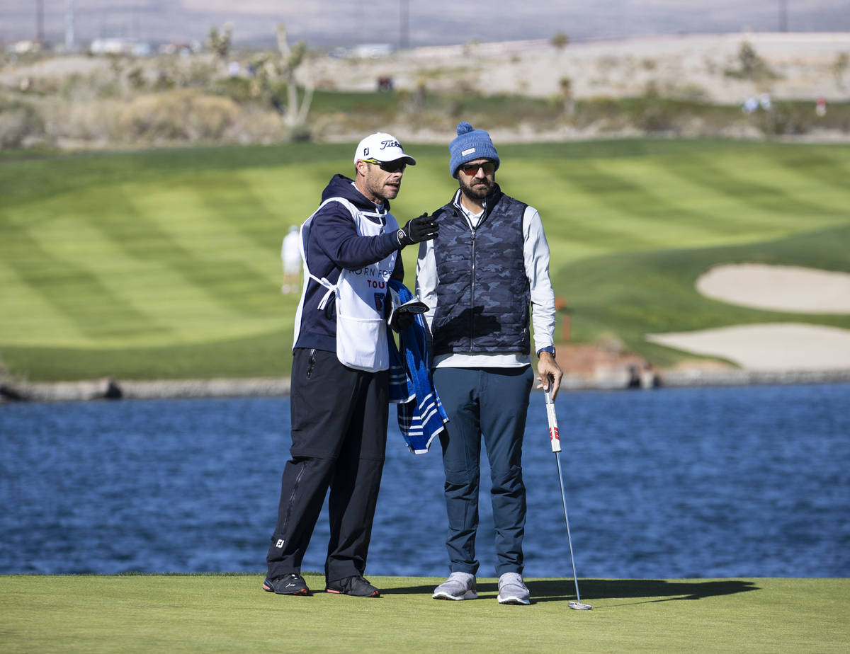 Chandler Blanchet of Jacksonville Beach, Fla., right, consults his golf caddy on fourth hole du ...
