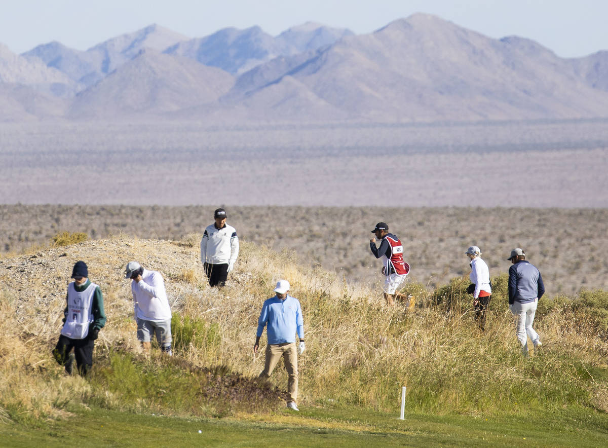 Triple-A golfers and their caddies search for a lost golfball during the first round of the MGM ...