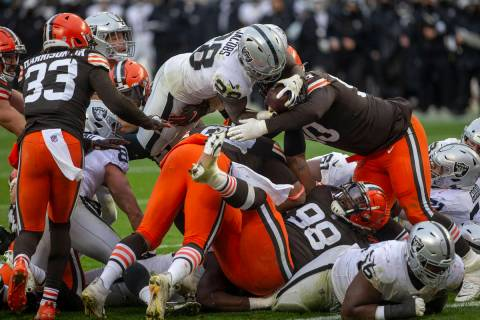 Las Vegas Raiders running back Josh Jacobs (28) leaps over against the Cleveland Browns defende ...