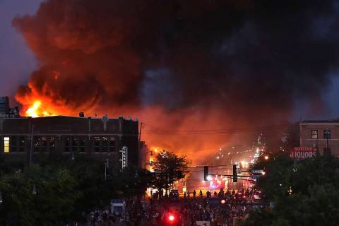 Seen from Hiawatha Avenue, a large fire burns Thursday, May 28, 2020, in Minneapolis during a t ...