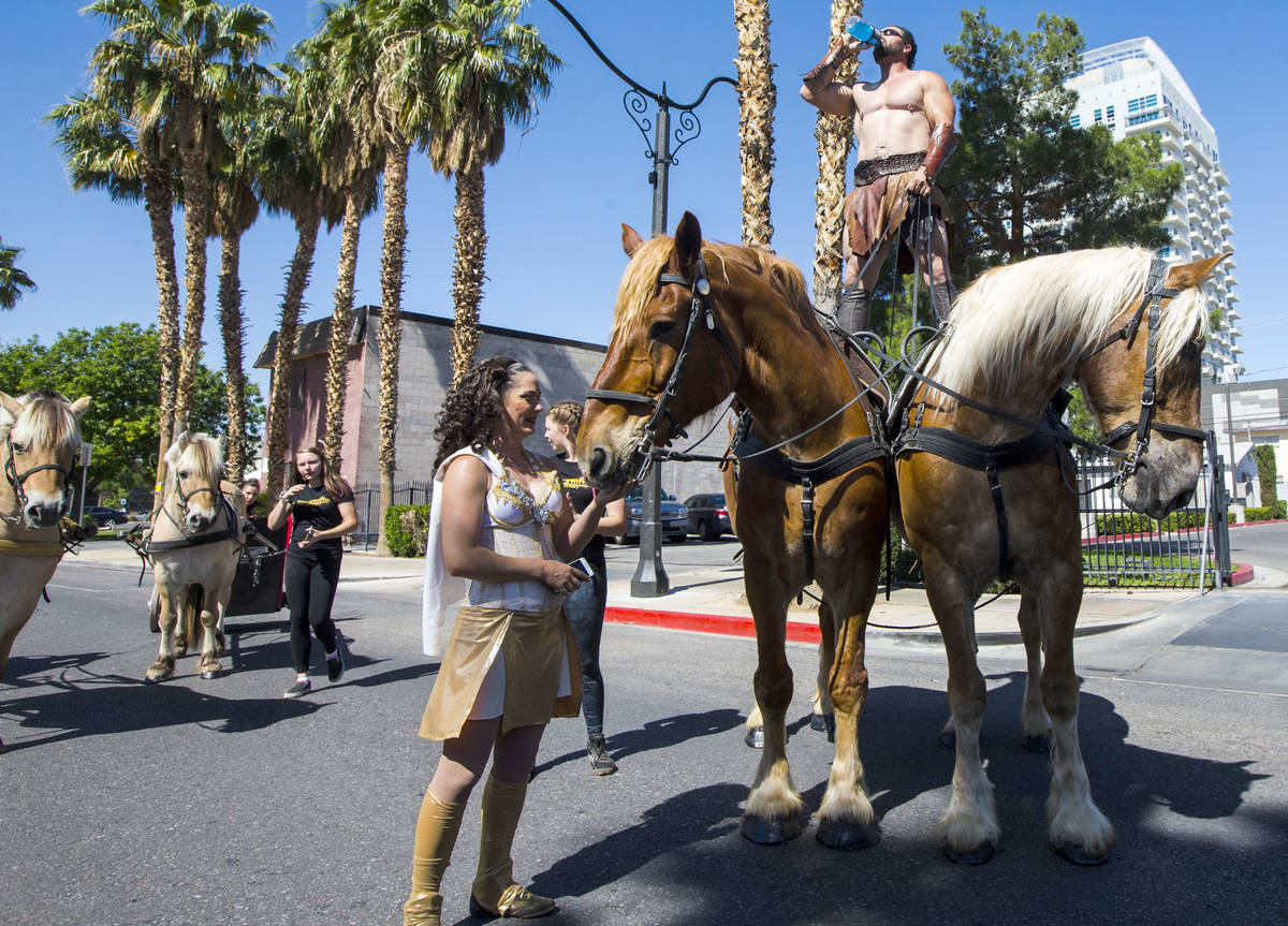 Erik Martonovich of Gladius the Show hydrates while standing on a pair of horses before the sta ...